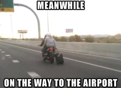 towing a suitcase behind a motorbike
